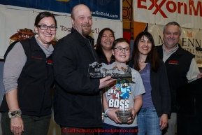 Aaron Burmeister recieves the Northern Air Cargo Herbie Nayokpuk award from Dave Karp, Sami Glascott and Cheryl Johnson of NAC as well as Michelle Bonham (Herbies grand daughter) and Bethany Thomas (Herbie's great-granddaughter) at the finishers banquet in Nome on Sunday  March 22, 2015 during Iditarod 2015.  (C) Jeff Schultz/SchultzPhoto.com - ALL RIGHTS RESERVED DUPLICATION  PROHIBITED  WITHOUT  PERMISSION
