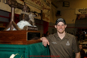 2015 Iditarod champion Dallas Seavey poses next to the Joe Redington Sr. first place trophy at the finishers banquet in Nome on Sunday  March 22, 2015 during Iditarod 2015.  (C) Jeff Schultz/SchultzPhoto.com - ALL RIGHTS RESERVED DUPLICATION  PROHIBITED  WITHOUT  PERMISSION
