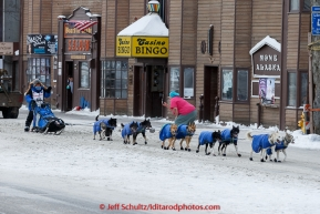 Cindy Gallea runs down Front Street and waves to a race fan taking her picture on her way to the finish line in Nome on Sunday  March 22, 2015 during Iditarod 2015.  (C) Jeff Schultz/SchultzPhoto.com - ALL RIGHTS RESERVED DUPLICATION  PROHIBITED  WITHOUT  PERMISSION