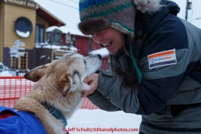 Linda Clarke, wife of musher Lachlan Clarke, gives one of their dogs attention at  the Nome finish chute shorlty after Lachlan finished on Sunday  March 22, 2015 during Iditarod 2015.  (C) Jeff Schultz/SchultzPhoto.com - ALL RIGHTS RESERVED DUPLICATION  PROHIBITED  WITHOUT  PERMISSION