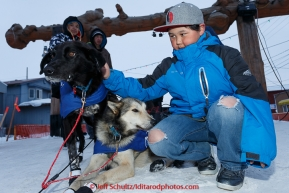 Young Mason Omiak of Nome pets a couple of Lachlan Clarke dogs shorlty after Lachlan finished the Iditarod at Nome on Sunday  March 22, 2015 during Iditarod 2015.  (C) Jeff Schultz/SchultzPhoto.com - ALL RIGHTS RESERVED DUPLICATION  PROHIBITED  WITHOUT  PERMISSION