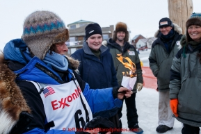 After successfully completing this year's Iditarod, Cindy Gallea ceremoniously burns last year's scratch paperwork at the finish line in Nome on Sunday  March 22, 2015 during Iditarod 2015.  (C) Jeff Schultz/SchultzPhoto.com - ALL RIGHTS RESERVED DUPLICATION  PROHIBITED  WITHOUT  PERMISSION