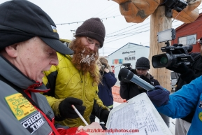 Trent Herbst signs in at the finish line in Nome on Sunday  March 22, 2015 during Iditarod 2015.  (C) Jeff Schultz/SchultzPhoto.com - ALL RIGHTS RESERVED DUPLICATION  PROHIBITED  WITHOUT  PERMISSION