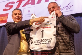 Iditarod board member Danny Seybert and Iditarod CEO Stan Hooley hold up a #1 bib with an honorary symbol