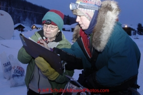 Thursday March, 2012  Perinnial Tokotna checker, Frankie Sayers, signs out Jodi Bailey from her 24 hour layover at the Takotna checkpoint.   Iditarod 2012.