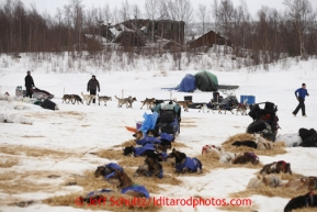 Allen Moore leaves on the Iditarod River with delapidated buildings of the ghost town of Iditarod in the background on Friday March 8, 2013.Iditarod Sled Dog Race 2013Photo by Jeff Schultz copyright 2013 DO NOT REPRODUCE WITHOUT PERMISSION