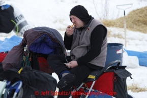 Jerry Sousa eats a snack while sitting on his sled at the halfway checkpoint of Iditarod on Friday March 8, 2013.Iditarod Sled Dog Race 2013Photo by Jeff Schultz copyright 2013 DO NOT REPRODUCE WITHOUT PERMISSION