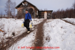 Brad VanMeter takes musher food bags to the trash pile. Due to the warm temperatures volunteers have sandeed the walkway hill trails with dirt at the halfway checkpoint of Iditarod on Friday March 8, 2013.  Iditarod Sled Dog Race 2013Photo by Jeff Schultz copyright 2013 DO NOT REPRODUCE WITHOUT PERMISSION