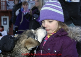 Thursday March 15, 2012   Young Stephanie Daniel from Nome gets a kiss from a Buser dog in the finish chute shortly after Rohn and Martin finished at a tie for 18th place. Iditarod 2012.