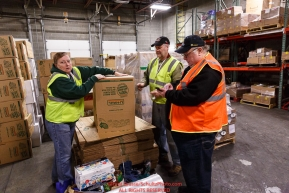 Iditarod volunteers Dan Paige and Pam Jacobs sort and repackage human food and supplies for the trail volunteers to eat and use at each of the checkpoints on the 2018 Iditarod. The sorting is going on at the Airland Transport warehouse facilities in Anchorage Alaska on Friday  February 19, 2017.