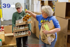 Iditarod volunteers sort and repackage human food and supplies for the trail volunteers to eat and use at each of the checkpoints on the 2017 Iditarod. The sorting is going on at the Airland Transport warehouse facilities in Anchorage Alaska on Friday  February 17, 2017.Photo by Jeff Schultz/SchultzPhoto.com  (C) 2017  ALL RIGHTS RESVERVED