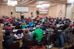 Mushers listen to Race Manager and Marshal Mark Nordman at the mandatory musher meeting at the Lakefront Anchorage hotel in Anchorage, Alaska. Thursday February 28, 2019 Photo by Jeff Schultz/  (C) 2019  ALL RIGHTS RESERVED