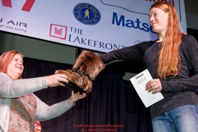 Kristy Berington picks her drawing position from a mukluk at the pre-race musher drawing banquet at the Dena'ina convention center in Anchorage, Alaska prior to the 2019 Iditarod Trail Sled Dog RacePhoto by Jeff Schultz/  (C) 2019  ALL RIGHTS RESERVED