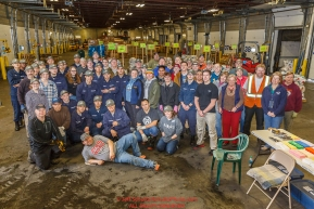 Iditarod volunteers pose for a group photo during the food drop day.  The goal is to unload, weigh, organize and stack the mushers food bags destined for the checkpoints on the 2017 Iditarod at the Airland Transport warehouse facilities in Anchorage Alaska.Wednesday February 15, 2017.Photo by Jeff Schultz/SchultzPhoto.com  (C) 2017  ALL RIGHTS RESVERVED