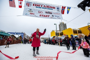 The original Teacher on the Trail Finney cuts the ceremonial ribbon during the ceremonial start of the 2018 Iditarod in Anchorage, Alaska on Saturday, March 1 2018.Photo by Jeff Schultz/SchultzPhoto.com  (C) 2018  ALL RIGHTS RESERVED
