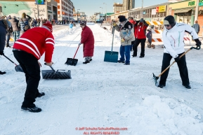 Volunteers shovel snow across the street during the Ceremonial Start in Anchorage on Saturday March 4, 2017 Photo by Jeff Schultz/SchultzPhoto.com  (C) 2017  ALL RIGHTS RESVERVED