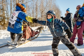 Young Ayden Tuttle gives a high-five to Mellisa Stewart on the bike/ski trail during the Ceremonial Start of the 2017 Iditarod in Anchorage on Saturday March 4, 2017 Photo by Jeff Schultz/SchultzPhoto.com  (C) 2017  ALL RIGHTS RESVERVED