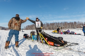 Joar Leifseth Ulsom gives a high-five to his friend Terry McCoy on Long Lake amongst the crowds during the Official Re-Start of the 2018 Iditarod Sled Dog Race in Willow, Alaska on March 04, 2018. Photo by Jeff Schultz/SchultzPhoto.com  (C) 2018  ALL RIGHTS RESERVED