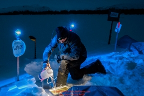 Mats Pettersson gets water from a hole in the lake during the early morning hours at the Finger Lake checkpoing on Monday March 05, 2018 during the 2018 IditarodPhoto by Jeff Schultz/SchultzPhoto.com  (C) 2018  ALL RIGHTS RESERVED