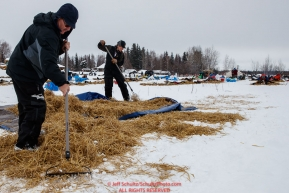 Checkpoint volunteers Marty Day and Erica Goad rake up used straw at the Nikolai checkpoint during the 2018 Iditarod race on Tuesday afternoon March 06, 2018. Photo by Jeff Schultz/SchultzPhoto.com  (C) 2018  ALL RIGHTS RESERVED