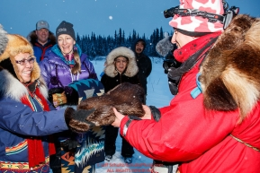 Nikolai resident Oline Petruska who made a set of beaver mitts and blanket present it to the first musher to arrive, Ryan Redington.  With her is Josie Owen of Alaska Air Transport at the Nikolai checkpoint during the 2018 Iditarod race on Tuesday March 06, 2018. Photo by Jeff Schultz/SchultzPhoto.com  (C) 2018  ALL RIGHTS RESERVED