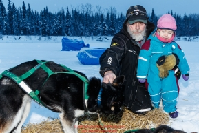 Long-time lead Nikolai checker John Runkle shows his 2-year old grandaughter Anavay Runkle a pair of Ryan Redington dogs at the Nikolai checkpoint during the 2018 Iditarod race on Tuesday March 06, 2018. Photo by Jeff Schultz/SchultzPhoto.com  (C) 2018  ALL RIGHTS RESERVED