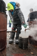 Wade Marrs gets steaming hot water for his dog food at the Nikolai checkpoint during the 2018 Iditarod race on Tuesday March 06, 2018. Photo by Jeff Schultz/SchultzPhoto.com  (C) 2018  ALL RIGHTS RESERVED