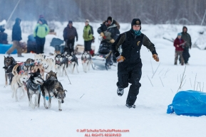 Trail volunteer Erica Goad runs in front of Ray Redington Jrs. team to a parking spot at the Nikolai checkpoint during the 2018 Iditarod race on Tuesday March 06, 2018. Photo by Jeff Schultz/SchultzPhoto.com  (C) 2018  ALL RIGHTS RESERVED