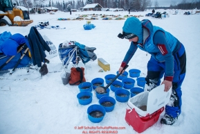 Anja Radano portions her dogs' food into bowls in the morning at the Nikolai checkpoint during the 2018 Iditarod race on Wednesday March 07, 2018. Photo by Jeff Schultz/SchultzPhoto.com  (C) 2018  ALL RIGHTS RESERVED