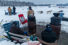 Nikolai residents man the hot water pots for musher's food as Marcelle Fressineau checks in during the morning at the Nikolai checkpoint during the 2018 Iditarod race on Wednesday March 07, 2018. Photo by Jeff Schultz/SchultzPhoto.com  (C) 2018  ALL RIGHTS RESERVED