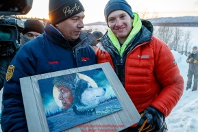 Wade Marrs recieves the Penair Spirit of Alaska award from Penair's president Danny Seybert for being the first person to the Ruby checkpoint during the 2017 Iditarod on Wednesday March 8, 2017.Photo by Jeff Schultz/SchultzPhoto.com  (C) 2017  ALL RIGHTS RESERVED