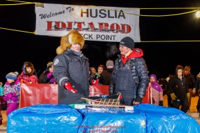 Mitch Seavey accepts the GCI Dorothy G. Page Halfway award from GCI rep Tara Wheatland at the Huslia checkpoint during the 2017 Iditarod on Thursday night  March 9, 2017.Photo by Jeff Schultz/SchultzPhoto.com  (C) 2017  ALL RIGHTS RESERVED