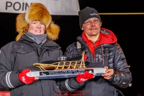 Mitch Seavey accepts the GCI Dorothy G. Page Halfway Award from GCI representative Tara Wheatland at the Huslia checkpoint during the 2017 Iditarod on Thursday night  March 9, 2017.Photo by Jeff Schultz/SchultzPhoto.com  (C) 2017  ALL RIGHTS RESERVED