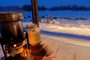 Water is heated for mushers to thaw their meals during a snowfall at the Iditarod checkpoint in the morning on Friday, March 9th during the 2018 Iditarod Sled Dog Race -- AlaskaPhoto by Jeff Schultz/SchultzPhoto.com  (C) 2018  ALL RIGHTS RESERVED