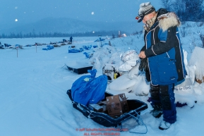 Volunteer checkpoint helper Rob Rose cleans up the yard during a snowfall at the Iditarod checkpoint on Friday, March 9th during the 2018 Iditarod Sled Dog Race -- AlaskaPhoto by Jeff Schultz/SchultzPhoto.com  (C) 2018  ALL RIGHTS RESERVED