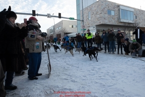 Martin Buser runs down 4th avenue past volunteers at a road crossing during the ceremonial start of the 2019 Iditarod in downtown Anchorage, Alaska on Saturday March 2.Photo by Jeff Schultz/  (C) 2019  ALL RIGHTS RESERVED