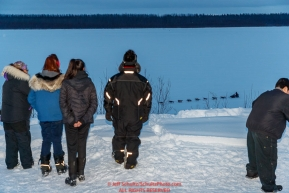 Local residents watch Nicolas Petit run down the Yukon River as he approaches the Kaltag village checkpoint on Saturday evening, March 10th during the 2018 Iditarod Sled Dog Race -- AlaskaPhoto by Jeff Schultz/SchultzPhoto.com  (C) 2018  ALL RIGHTS RESERVED