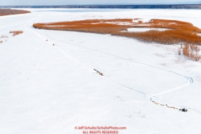 Two teams rest during their run up the Yukon River between the Grayling and Eagle Island checkpoints as two snowmachines travel by on Saturday, March 10th during the 2018 Iditarod Sled Dog Race -- AlaskaPhoto by Jeff Schultz/SchultzPhoto.com  (C) 2018  ALL RIGHTS RESERVED