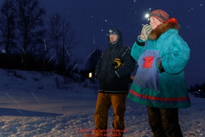 Volunteer checkers Brad VanMeter and Madeline Rubida call in out times to comms the early morning hours at the ghost-town checkpoint of Iditarod on Saturday, March 10th during the 2018 Iditarod Sled Dog Race -- AlaskaPhoto by Jeff Schultz/SchultzPhoto.com  (C) 2018  ALL RIGHTS RESERVED