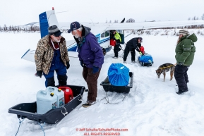 Volunteers unload supplies from Jerry Wortley's plane as dropped dogs are about to be loaded at the ghost-town checkpoint of Iditarod on Saturday, March 10th during the 2018 Iditarod Sled Dog Race -- AlaskaPhoto by Jeff Schultz/SchultzPhoto.com  (C) 2018  ALL RIGHTS RESERVED