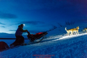 Linwood Fiedler and team run up the bank of the Yukon River and into the Kaltag checkpoint as dawn breaks on Sunday March 10th during the 2019 Iditarod Trail Sled Dog Race.Photo by Jeff Schultz/  (C) 2019  ALL RIGHTS RESERVED