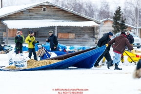 Volunteers move straw at the Huslia checkpoint during the 2017 Iditarod on Saturday morning March 11, 2017.  Photo by Jeff Schultz/SchultzPhoto.com  (C) 2017  ALL RIGHTS RESERVED