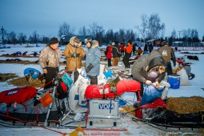 Volunteer vets read over the vet book as Lars Monsen checks in and out of the Huslia checkpoint during the 2017 Iditarod on Saturday morning March 11, 2017.Photo by Jeff Schultz/SchultzPhoto.com  (C) 2017  ALL RIGHTS RESERVED