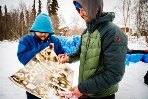Nicolas Petit signs an ExxonMobil Iditarod poster for a student at the Koyukuk checkpoint during the 2017 Iditarod on Saturday afternoon March 11, 2017.Photo by Jeff Schultz/SchultzPhoto.com  (C) 2017  ALL RIGHTS RESERVED
