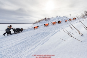 Martin Buser runs up the bank of the Yukon River and into the Kaltag village checkpoint on Sunday afternoon March 11th during the 2018 Iditarod Sled Dog Race -- AlaskaPhoto by Jeff Schultz/SchultzPhoto.com  (C) 2018  ALL RIGHTS RESERVED