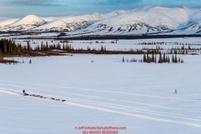 A team runs on the trail between Kaltag and Unalakleet with the Whaleback mountains in the background on Sunday evening March 11th during the 2018 Iditarod Sled Dog Race -- AlaskaPhoto by Jeff Schultz/SchultzPhoto.com  (C) 2018  ALL RIGHTS RESERVED
