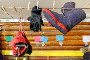 Musher gear is hung up to dry around the wood stove in the community center at the Kaltag village checkpoint on Sunday morning March 11th during the 2018 Iditarod Sled Dog Race -- AlaskaPhoto by Jeff Schultz/SchultzPhoto.com  (C) 2018  ALL RIGHTS RESERVED