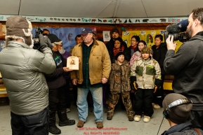 Richard Burnham, on behalf of the entire family accepts the Herbie Nayokupuk Spirit of Iditarod award for his father-in-law Austin Esmailka, from race judge Kevin Sakai at the Kaltag checkpoint during the 2017 Iditarod on Sunday morning March 12, 2017.Photo by Jeff Schultz/SchultzPhoto.com  (C) 2017  ALL RIGHTS RESERVED