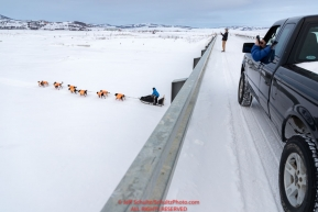Martin Buser runs under the bridge on the Kouwegok slough as locals take photos shortly after he left the Unalakleet checkpoint on Monday  afternoon March 12th during the 2018 Iditarod Sled Dog Race -- AlaskaPhoto by Jeff Schultz/SchultzPhoto.com  (C) 2018  ALL RIGHTS RESERVED