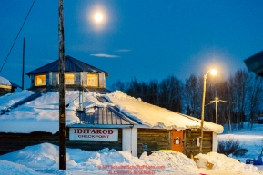 A full moon is in the sky over the community center at the Kaltag checkpoint during the 2017 Iditarod on Monday morning March 12, 2017.Photo by Jeff Schultz/SchultzPhoto.com  (C) 2017  ALL RIGHTS RESERVED
